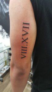 Tatuaggio Tattoo Numeri Romani tricipite