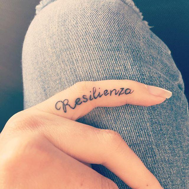 Tatuaggio Tattoo Resilienza scritta dito